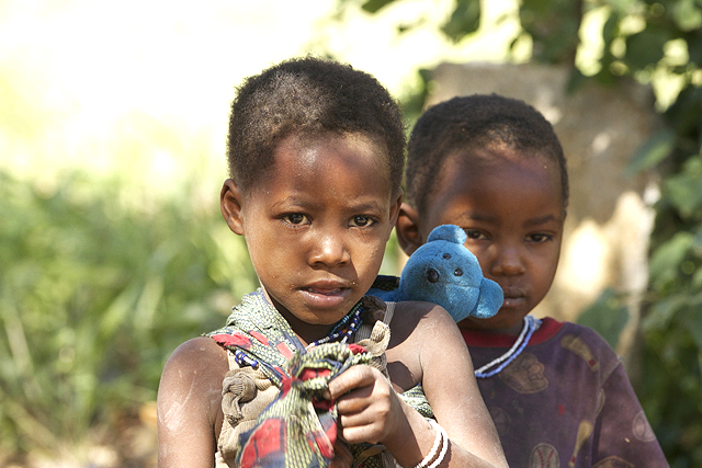 """Hadzabe Child with """"her baby"""" on her back."""
